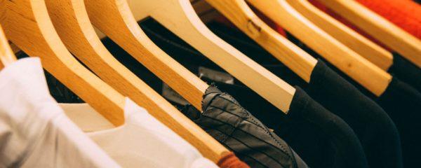 Des habits accrochés à des ceintres dans un magasin