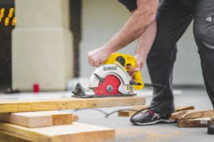 Un ouvrier du bâtiment en train de poncer du bois.