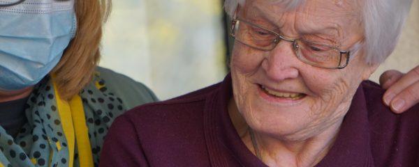 Une infirmière tenant un smartphone pour une dame âgée.