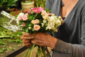 Une femme avec des fleurs en main.
